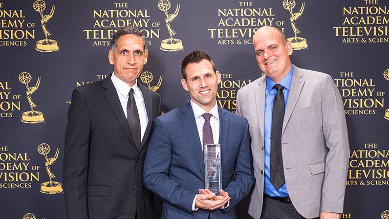 men posing with award at national academy of television awards